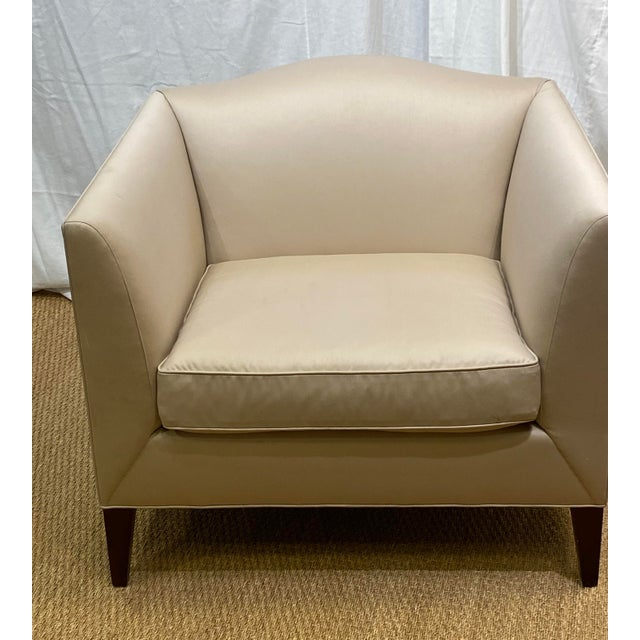 Contemporized camelback Club Chair with a butter knife arms. Loose Seat. Square tapered legs. Singularly outstanding, this...