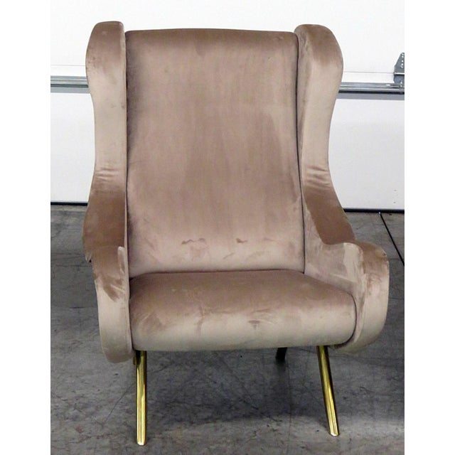 Pair of modern lounge chairs with velvet upholstery and brass legs.