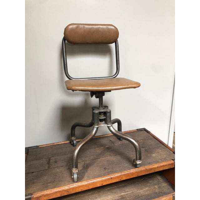 Adjustable swivel metal desk chair on wheels with leather seat and back from the 1940s.