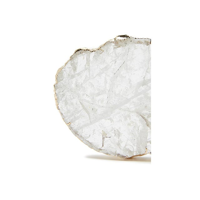Set of 2 coasters handmade from slabs of natural stone with pure silver tracing the asymmetrical edges. Protective rubber...