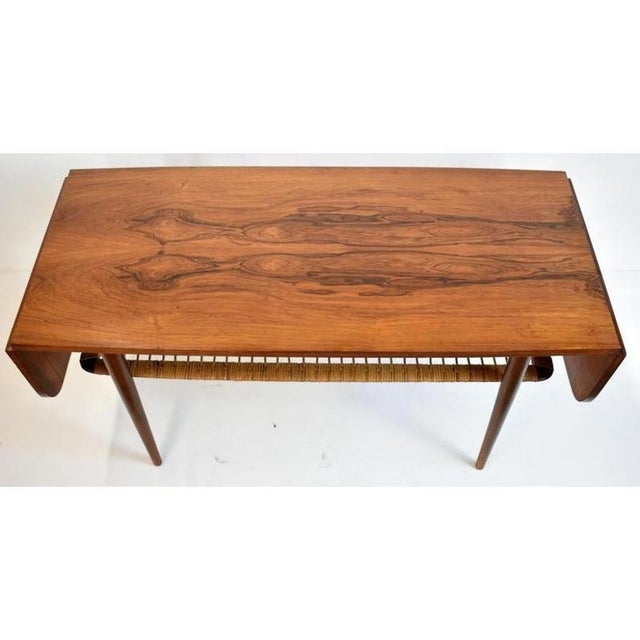 """Mid-century modern coffee table features woven rattan lower shelf and 8"""" drop leaves on each end. It measures 21-1/2"""" tall..."""