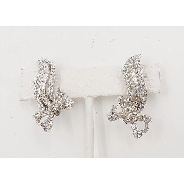 """1950s rhodium plated round and baguette rhinestone clip back earrings. Marked """"Kramer of N.Y."""" Measure:1.5 inches L x 0.75..."""