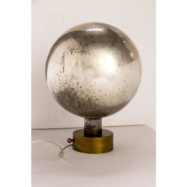 A striking antique mercury glass sphere, newly mounted as sculptural lighting on an antiqued brass base. This piece looks...