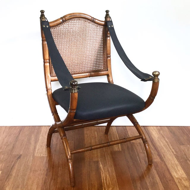1970s Drexel campaign or safari style chair with sling arms, faux bamboo frame, and a cane back. It has been completely...