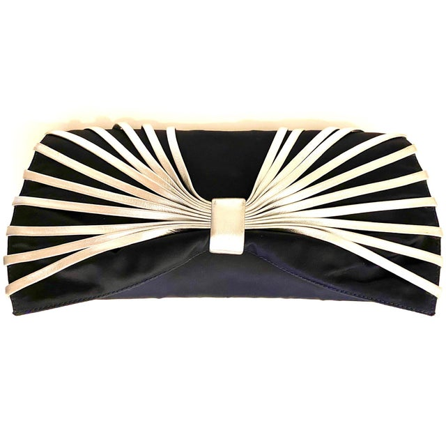 Unique styling in this recent Rodo clutch. Composed of navy silk, it has a bow design on the front, accented in soft...