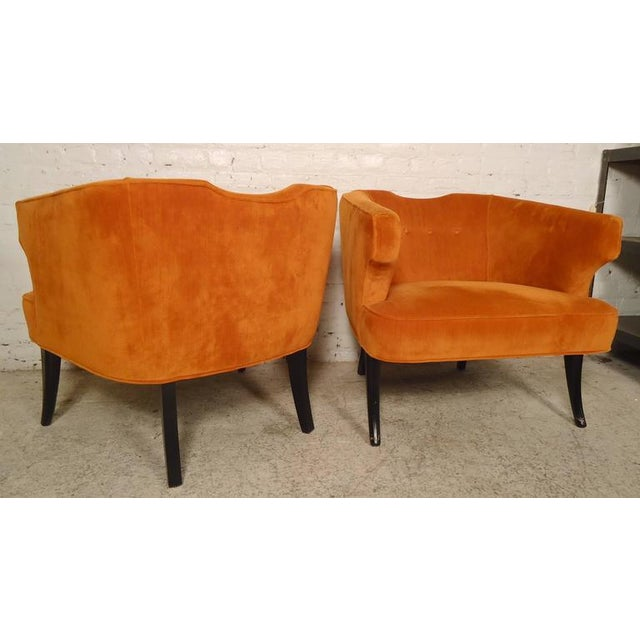 "Pair of vintage modern upholstered chairs with unusual rounded back and ""wing"" style arms. Upholstered in vibrant orange..."