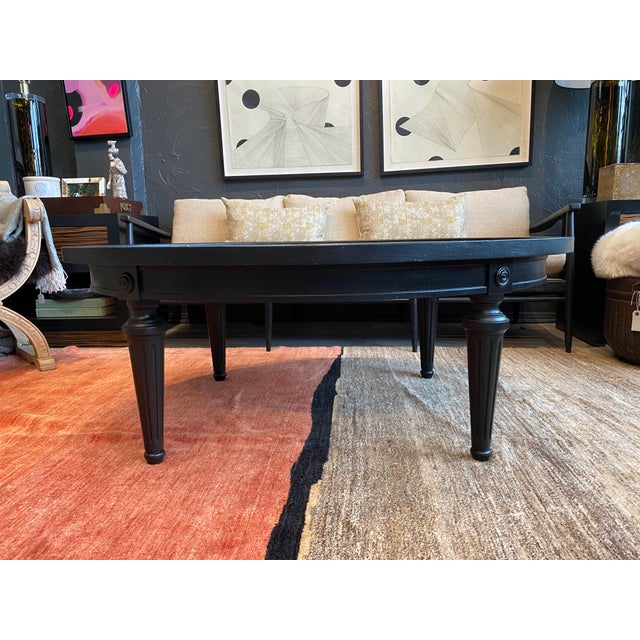 Oval Hollywood Regency Coffee table with an ebony stained body and gorgeous antique speckled mirror top.
