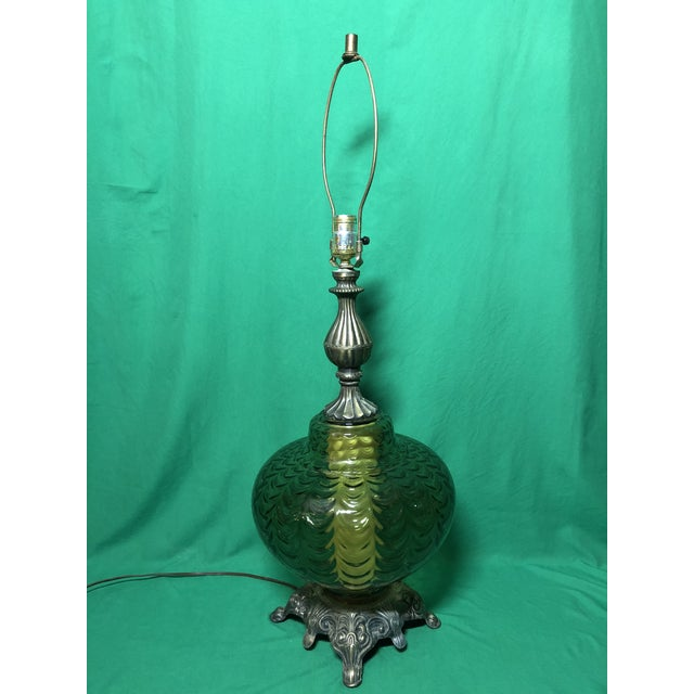 A Hollywood regency midcentury table lamp with a large green base piece with interior lighting.