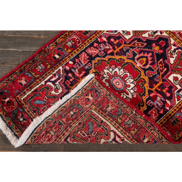 A Beautiful Vintage Heriz rug with a red field and multi-color accents in all-over multi medallion design. This rug...