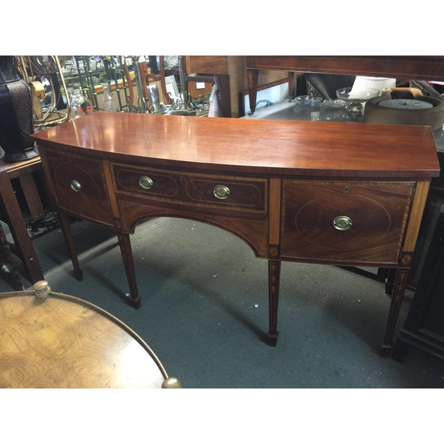 Mahogany and satinwood inlaid bow front sideboard by Baker Historic Collection. This fine custom quality sideboard is made...