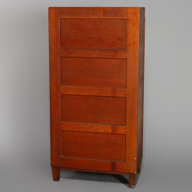 An antique Arts & Crafts mission oak filing cabinet by Yawman & Erbe offers paneled construction with 10 drawers having...
