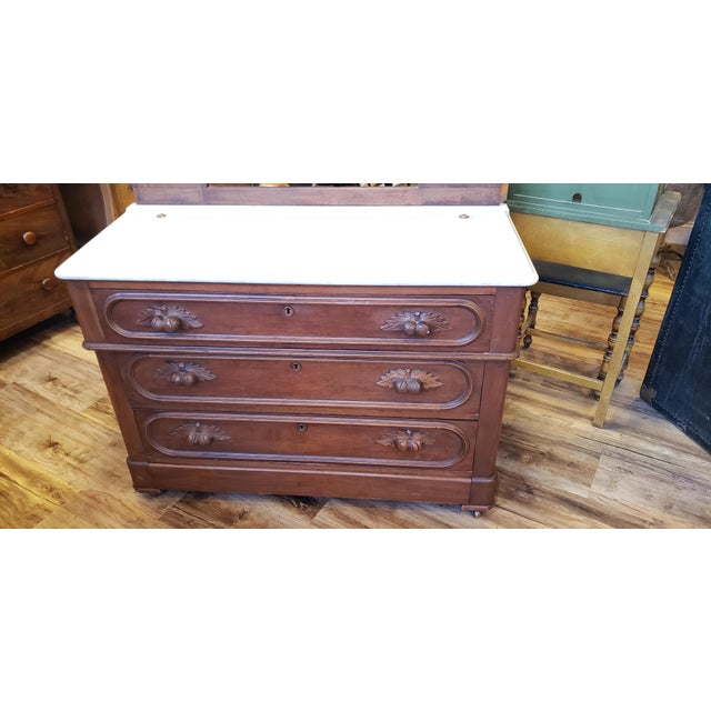 This beautiful antique dresser is Eastlake Victorian style in walnut. Underneath the marble top is the date of 1898 and on...