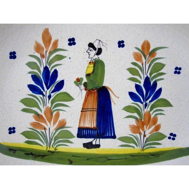 A vintage earthenware faience oval bowl, HenRiot Quimper, France, circa 1960's. The center shows a femme de la campagne, a...