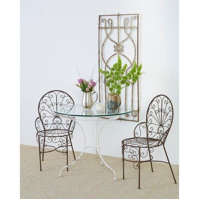 Set of four stunning iron garden or patio chairs featuring a fan back or peacock style. Made in the manner of Salterini....