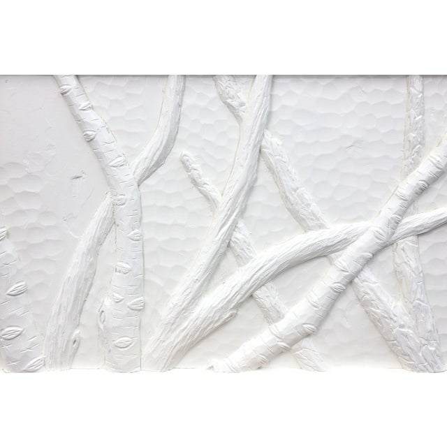 A wall hanging of branch reliefs, painted in white with a white frame.