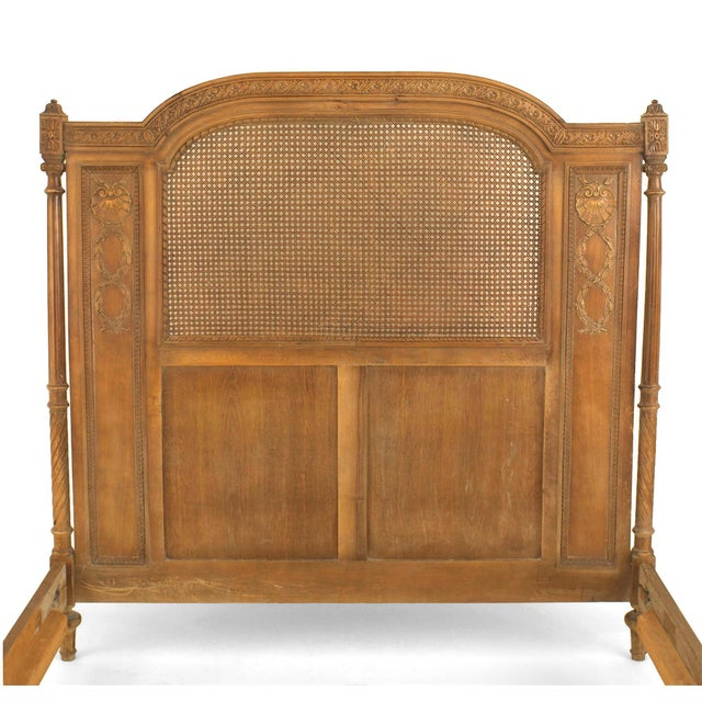 Turn of the century French Louis XVI style walnut full size bed with a cane panel headboard and footboard with rounded...