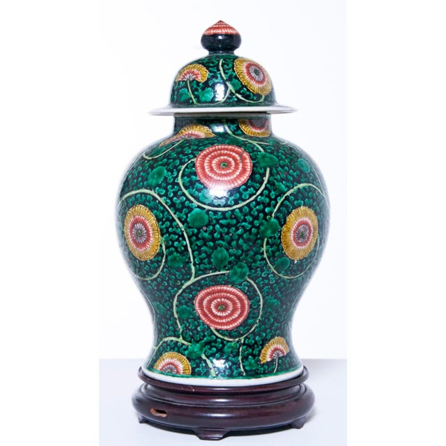 Famille verte porcelain temple jar with cover on new wood stand. coral, yellow , mauve, white and light green on black and...