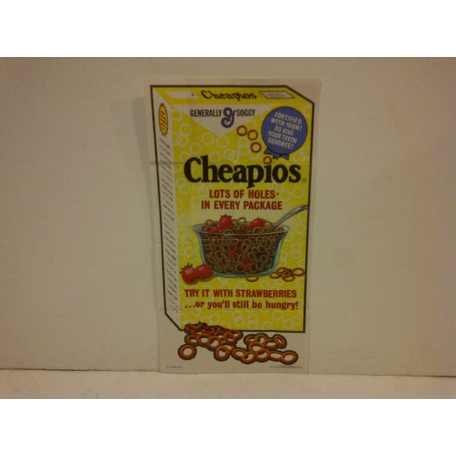 "A rare, wacky package poster for ""Cheapios"". The silly tagline reads, ""Lots of holes in every package"". Numbered 21 of 24...."