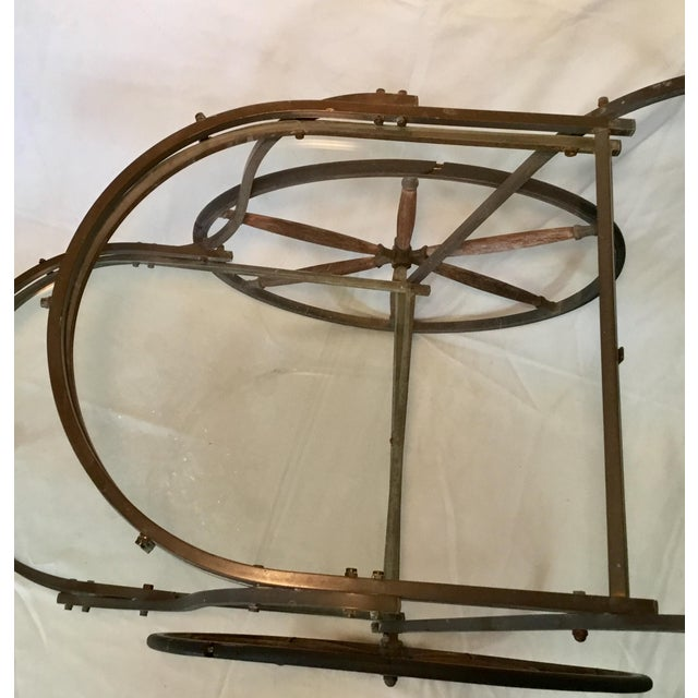 This bar cart is distinctive and sleek, with a sturdy bronze frame and wooden spoked wheels. The handle also has a section...