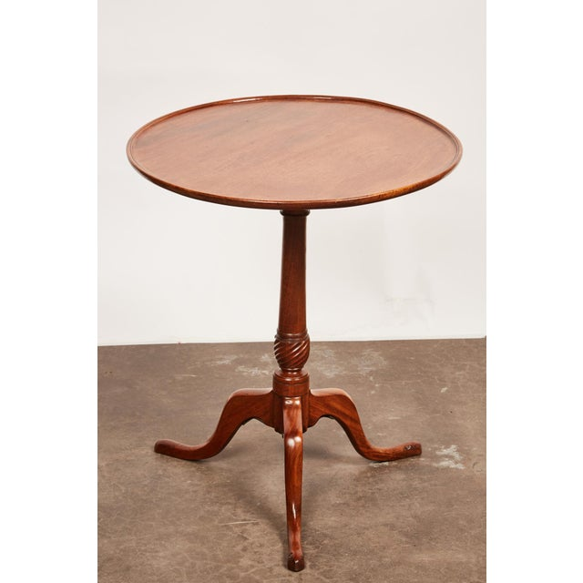 This late 18th century George III mahogany occasional pedestal table features a molded dished circular top above a turned...