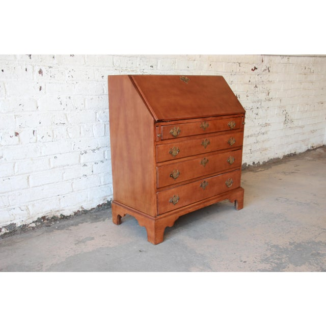 Offering a stunning 18th Century Early American cherry wood drop-front secretary desk. The desk features solid wood...