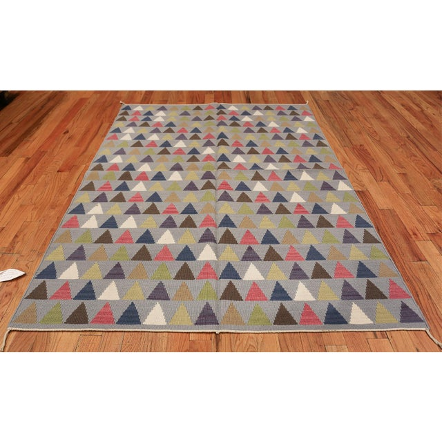 Deftly styled with a bold, modern flair, this charming vintage Swedish Kilim takes a simple flat-weave repeating pattern...