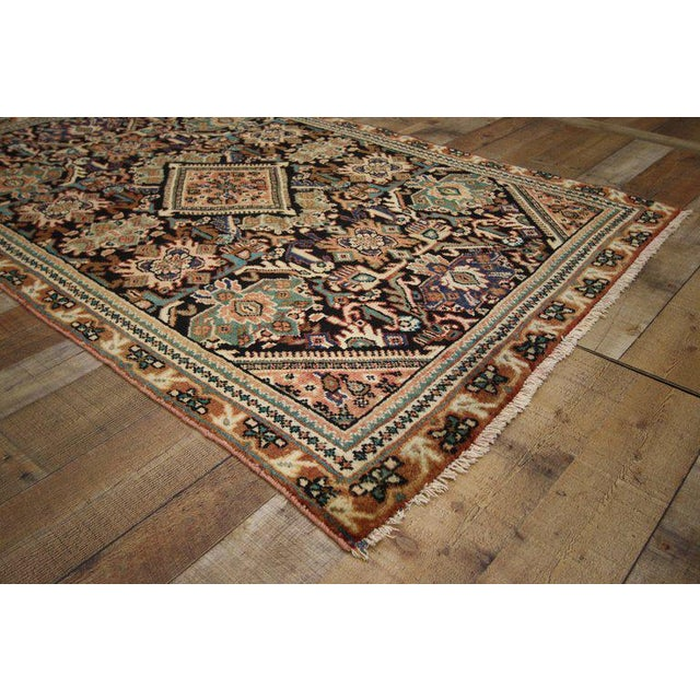 This hand-knotted wool vintage Persian Mahal rug features a diamond medallion with comb-like edges and complementary...