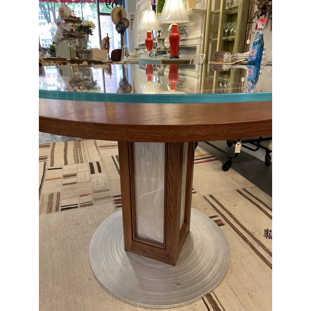 This is a beautiful vintage accent table. The base is a brushed steel circle with a wooden pedestal attached. The top is a...