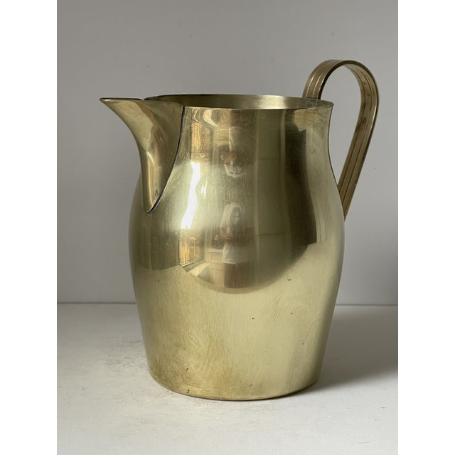 Brass pitcher designed by Tommi Parzinger for Dorlyn. Circa 1950's. Has tiny dent.Marked on the bottom.
