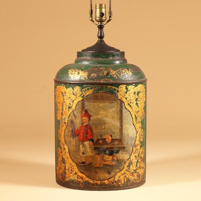 An English tole tea canister: the green ground with gilt decoration and centering a painted panel depicting a Chinese...