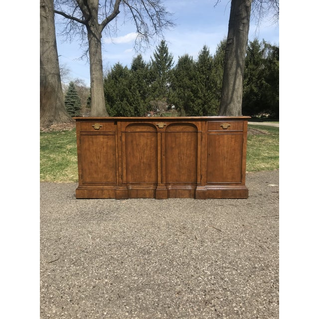 Walnut credenza with four doors and three drawers. Doors open and lock with key. Fine craftsmanship with concave doors and...
