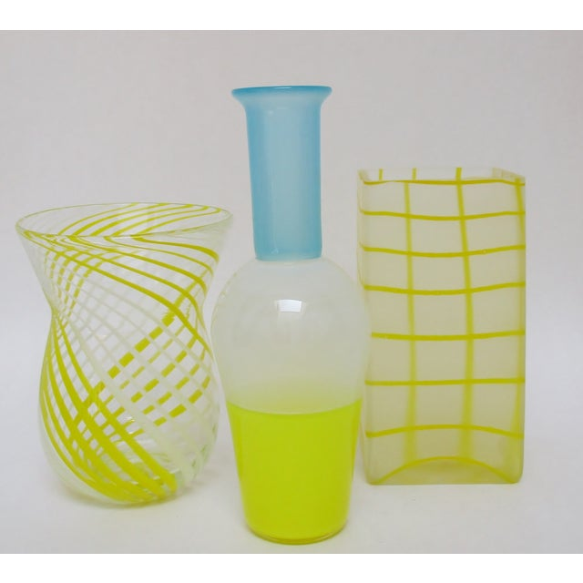A collection of coordinating blown glass vases in three styles, each with a bright yellow motif. The taller slender vase...