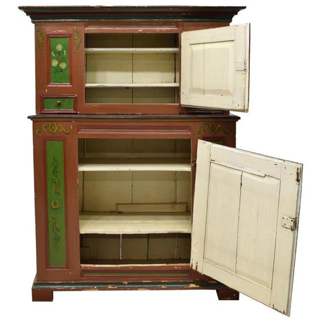 This lovely painted Swedish country pine cupboard, c. 1800, features polychrome paint and dated 1798. It has a step-back...