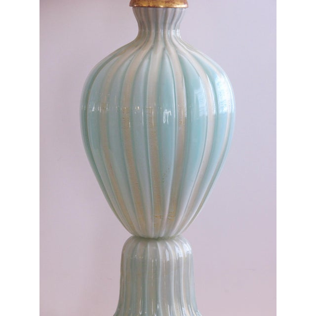 Of ribbed ovoid shape with gold aventurine inclusions all over a splayed gilt wood base