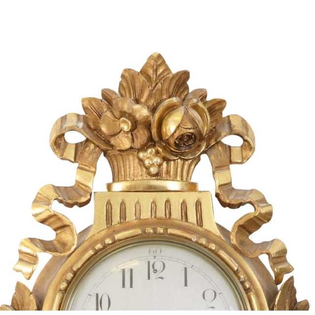 Gustavian style Swedish wall clock. This antique Swedish wall clock was made 1900 or earlier and has hand carved and...