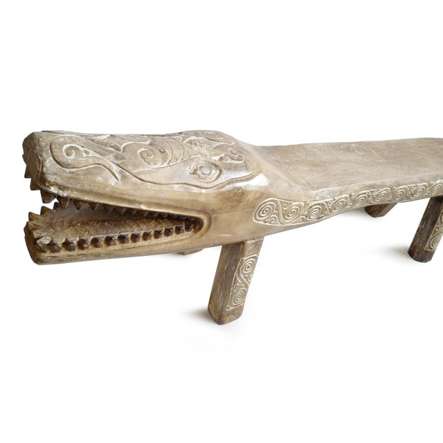 Impressive large hand carved crocodile bench. Made from a log with detailed tribal design patterns. Natural wood tone with...