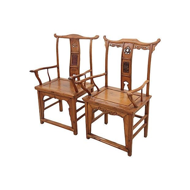 An antique pair of Yolk chairs made of elm. The first is more masculine with wider and simple carvings, the second is...