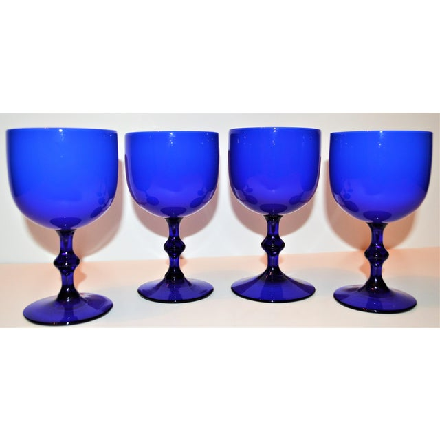 This is set of four cobalt blue Italian Carlo Moretti goblets! These glasses are an incredibly vibrant blue cased glass...