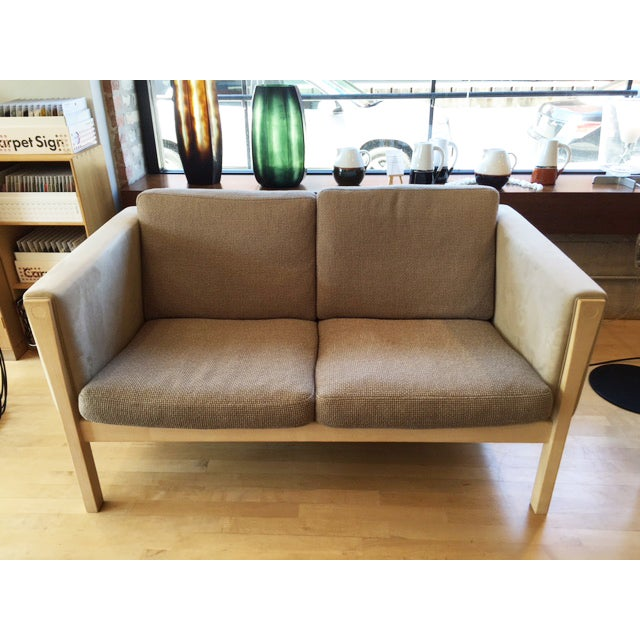 A CH162 Sofa by Hans Wegner that was manufactured by Carl Hansen, 2012 - Features original Kvadrat Perla #286 cushions and...