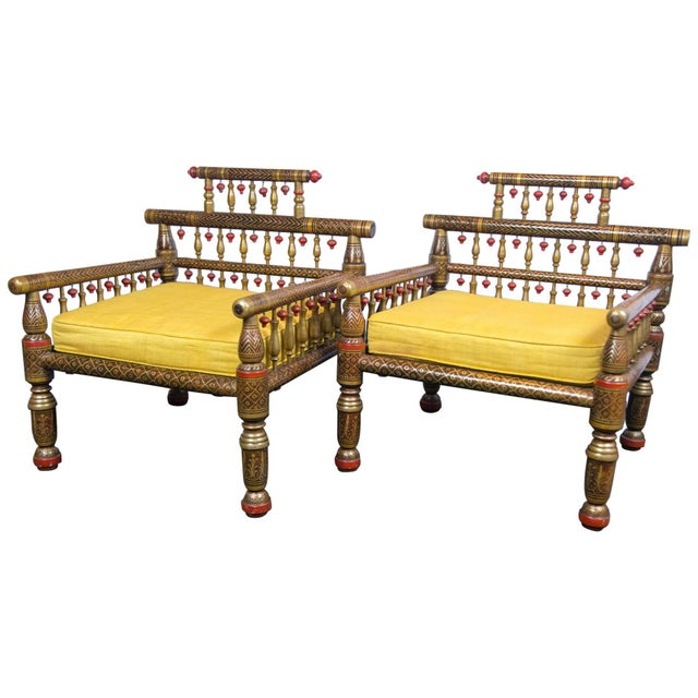 "Pair of fanciful Anglo-Indian style armchairs with an intricate painted finish and carved wood ""tassels""."