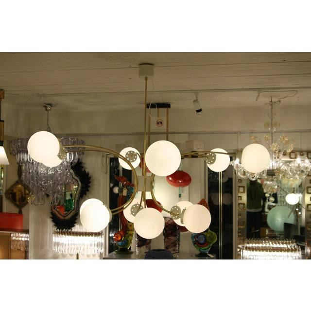 A bespoke ceiling light, 12 white satin blown glass shades, brass structure. Italian design ca. 20th Century. MEASUREMENTS...