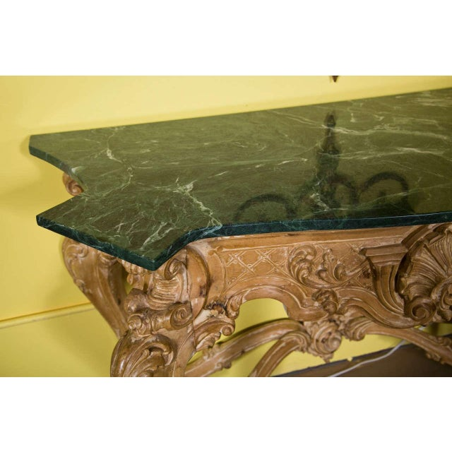 Pair of exceptional bleach wood console tables, circa 1940s. The shaped dark green marble atop an elaborately carved base,...
