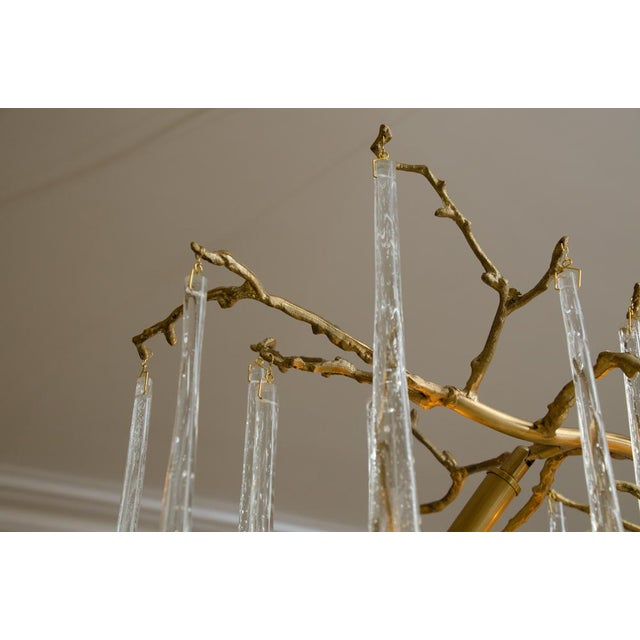 Very striking chandelier with gilt metal branches suspending long crystal drops