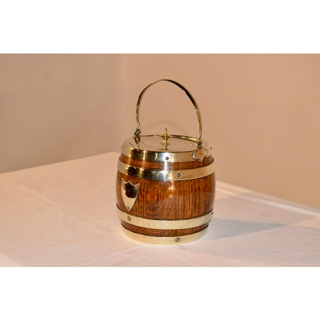 English oak biscuit barrel with silver plated lid and banding. It retains the original porcelain liner inside.