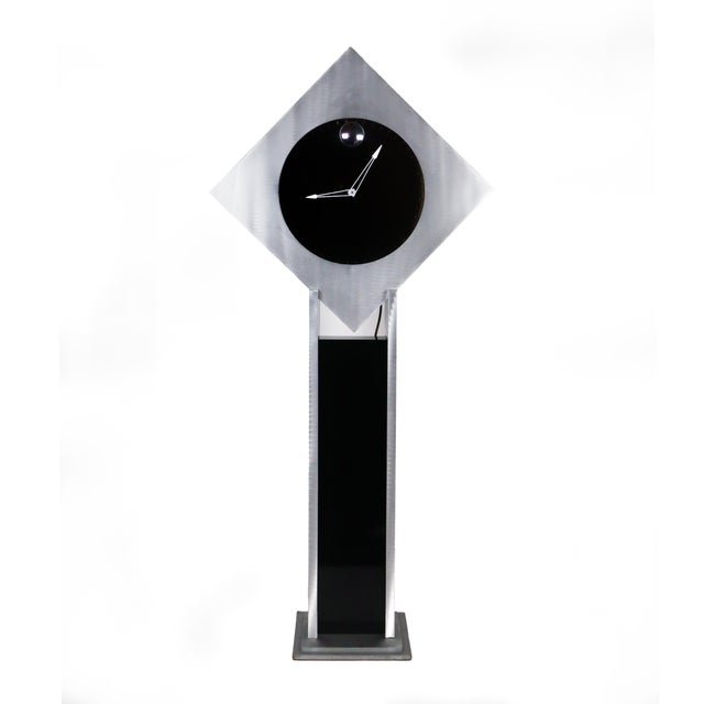 A unique and stunning diamond-shaped frame in brushed aluminum with two way mirrored clock face, mirrored interior, and...