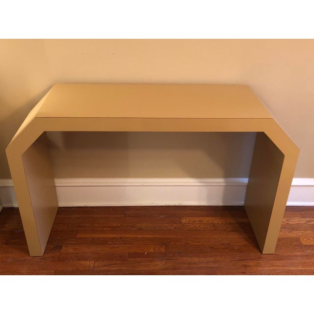 This substantial console table is a gold-hued Formica and hails from the 1980's. It remains in perfect condition.