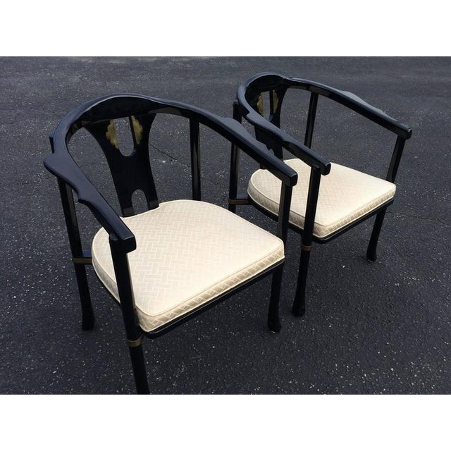 Pair of Asian style lacquered armchairs by Century. Classic black and white design with brass accents on the back and on...