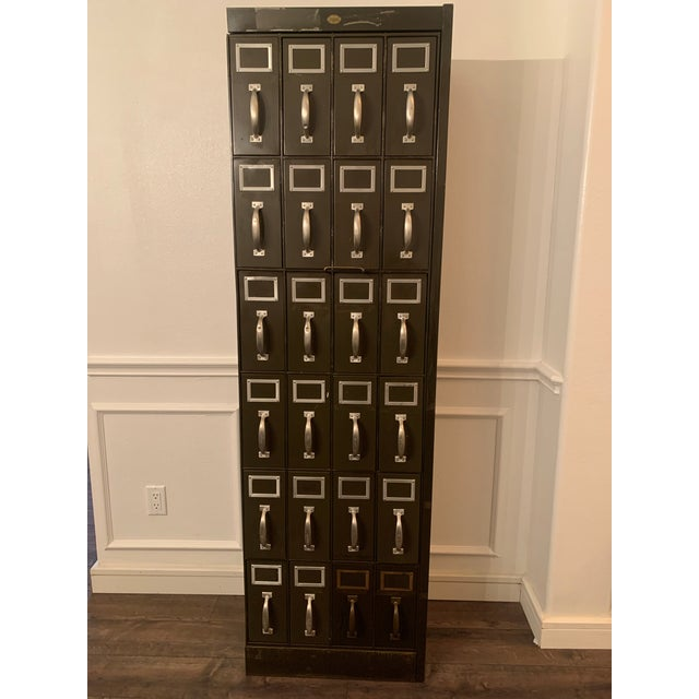A Large Vintage metal courthouse ledger file cabinet with 24 drawers arranged veritcally in 6 rows of 4. With a classic...