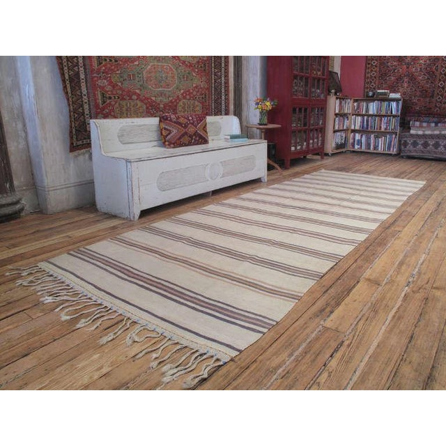 An old tribal floor cover from Central Turkey, in characteristic long format, with colorful bands on natural, un-dyed...