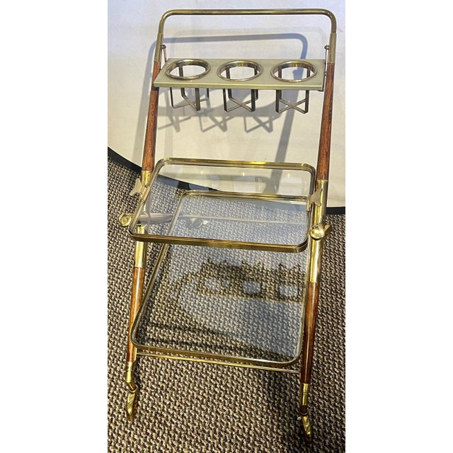 Mid-Century Modern bar cart. Teak and brass bar cart or serving cart with bottle holders and glass holders as well as...